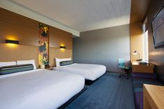 Enjoy an easy breezy night in our spacious Dulles airport hotel guest room featuring two queen beds, nine-foot ceilngs, large windows, walk-in showers, and Bliss® Spa amenities.