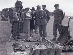 Shortly before D Day in late May 1944 - King George IV with Queen Elizabeth and the 18 year old Princess Elizabeth visiting the 6th Airborne Division. A young sapper officer is explaining the contents of a hand pushed trolley.