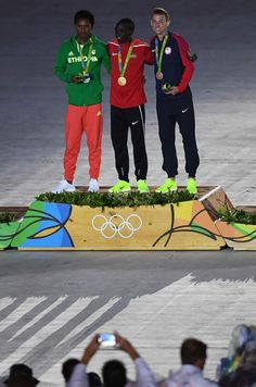 (L to R) Silver medalist Feyisa Lilesa of Ethiopia, gold medalist Eliud Kipchoge of Kenya and bronze medalist Galen Rupp of the United States celebrate on the podium at the medal ceremony for the Men's Marathon during the Closing Ceremony on Day 16 of the Rio 2016 Olympic Games at Maracana Stadium on August 21, 2016 in Rio de Janeiro, Brazil.