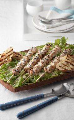"Grilled Chicken Caesar Salad — Mix it up at your next cookout with a delectable mashup of kabobs and Caesar salad: juicy chicken marinated in creamy dressing, and ""croutons"" toasted on the grill."