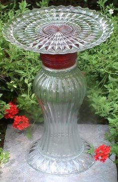 Glass Garden Ornament Bird Bath Feeder Crystal Red Mary  The name given this piece is Mary. It includes 4 pieces of glass, accented with a red accent support and a diamondpoint cut glass pattern in the underside of the top plate. Center piece is vertically ribbed from top to bottom. It stands approximately 15 inches high and 10.25 inches wide. Best use for this piece is as a bird feeder, bird bath, or as a pillar or plant stand.