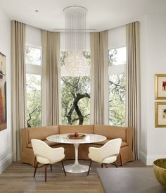 Hang the drapes at the top of the wall, not the window.  Give height to the room...drapery ideas for bay windows