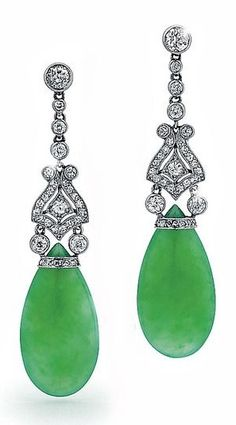 A Pair of Art Deco Jade and Diamond Pendant Earrings, circa 1925. Each suspending a polished jade, below a diamond set motif, from an articulated diamond collet line and diamond collet surmount, marked with serial number. #ArtDeco #earrings