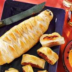 "Yummy Mummy Calzones Recipe -Family favorite pizza toppings are the not-so-spooky surprise inside these clever calzones from our Test Kitchen. If you serve these on wood ""coffins"" like we did, be sure to line the surface with plastic wrap or waxed paper."