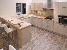 Vue sur l'ensemble de l'espace cuisine de cet appartement. Les plans de travail et certains placards sont en bois de chêne. La cuisine est lumineuse, épurée et fonctionnelle.