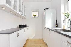 Une cuisine étroite blanche avec un sophistiqué plan de travail stratifié gris