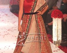 Neha Dhupia at Gitanjali Show India International Jewellery Week 2013. She donned blood red Long Frock and paired them with a purple velvet Lehenga with wrap-around belt tied along with the dupatta at the waist. The elegance and glamour of this outfit is undeniable. Her top bodice is plain but alot of decorations are done at the flares. Her hairbun looks fabulous with the kundan maangtika while studded necklace and earrings gave her complete look.