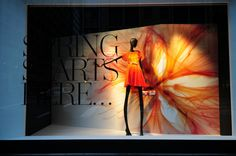 2013 Lord & Taylor  Spring windows, New York visual merchandising - another window display that uses the element of enlargement. The backdrop of the window display is an enlarged photo or idea of the dress. Whats unique about the window display is that the spotlight on the orange dress and the backdrop has created a focus point as the remaining background and mannequins are in black. No fancy elements is involved, and it has linked the dress with the backdrop very well.
