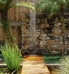 Em vez de piscina, a arquiteta Flavia Petrossi preferiu aproveitar a área externa com área gourmet, fonte, espelho d'água, chuveirão e muitas plantas