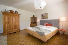 Modernes Zirbenbett in der Altbauwohnung im Box-Springbett Look. Der Mix aus verschiedenen Stilen und alten Möbeln passt perfekt in die Salzburger Stadtwohnung.