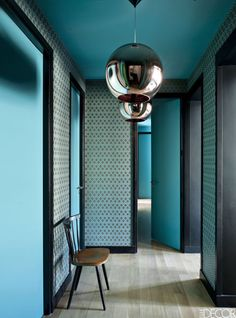 For the retro inspired, geometric-print entrance hall of a Paris apartment, designers Anne Geistdoerfer and Flora de Gastines of Double G incorporated framed pan­els of Cole & Son's Hicks' Hexagon turquoise wallpaper with striking black trim. The Copper Shade silver pendant lights are by Tom Dixon.