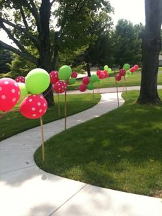 balloons tied on stakes down a pathway in the party's theme colors. Charming.