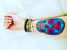 Blue sugar skull tattoo with diamond on woman's forearm