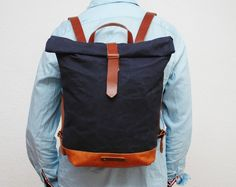 Waxed canvas backpack,navy color,use handles, base closures leather trimmings Golden antique gold color and the interior in cream cotton with