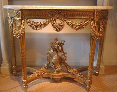 Fine, French, Louis XVI period, demi-lune console table. In solid, carved giltwood, having four, tapered, fluted legs joined by a stretcher centered with floral urn, the apron elegantly carved with bows and garlands, having a Carrera marble top. From Paris circa 1780.