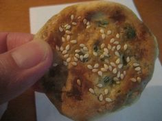 "The famous ""Illumination Biscuit"" (guangbing) hot out of a roadside oven in Jianou, Fujian Province, China. Thin, flaky piping hot savory flat biscuit with scallions and sesame seeds."