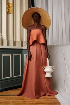 """The hats and straw bags were inspired by a Mediterranean vacation over the summer—while on a boat with Nasiba Adilova, the Russian beauty's wide brim straw topper flew into the sea, prompting the captain to turn the boat around and send someone into the water to retrieve it. At that moment, Assoulin explains, """"I knew we had to have straw hats."""" Here, a high drama topper is paired with a rust colored ball gown skirt and matching thin strapped tank. - HarpersBAZAAR.com"""
