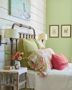 Shiplap accent wall in this antique farmhouse style bedroom. Love the green and pink decor!