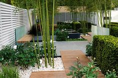 decking and rock planters, love the modern white fencing too. Will brighten up the shady area