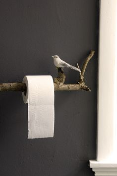 A unique toilet paper holder with a twig and a bird.