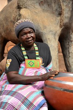 The famous Venda potter,-Rebecca Matibe sits-in her garden with one of-her sculptures behind her and one of her traditional pots We Are The World, People Of The World, African Pottery, African Artists, African Design, Ceramic Artists, African Women, Artist At Work, Black History