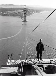 A man standing on the first cables during the construction of the Golden Gate Bridge, with the Presidio and San Francisco in the background. (1936)