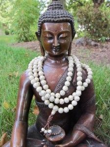 A wonderful way to display and keep your malas. I do the same thing with my Buddha statue!