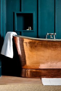 Dark blue against a copper soaking tub makes for a moody bathroom that encourages a soak