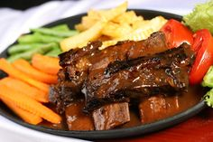 Beef steak with black pepper sauce, mashed potatoes and vegetable stew