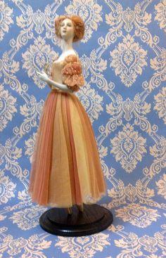Augusta ( di Alexandra Koukinova) La silhouette dell'abito è simile alle forme degli abiti del Rinascimento. Realizzato con magnifiche maniche importanti è costituito da un tulle in seta a rete multi-colore e multi-strato mentre il corpetto è in raso. Il tutù' è decorato con perle, perline oro, sottili fili d'oro e con fiori di seta fatti a mano. orcellana biscuit. Edizione limitata di 25 esemplari ;altezza circa cm 44,00