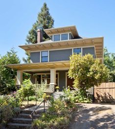 """The 1907 American Foursquare has """"artistic"""" details inside and out. The body color is 'Gloucester Sage,' trim is 'Pittsfield Buff,' and sash and doors are 'Black Forest Green,' all from Benjamin Moore."""