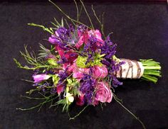 A Vows, Estes Park Original!  Wildflower theme bouquet in various shades of purples and lavenders, accented in twigs for a more asymmetrical look. Finished with a real bark wrap tied in braided twine.