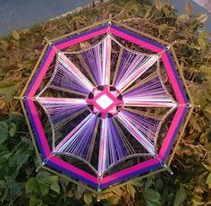 Mandala tecida em fios de linha e varetas de bambu.