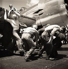 Crewmen hastily drag plane with flat tire down flight deck of USS Lexington (CV-16) to make way for next plane to land. 1944 or 1945.
