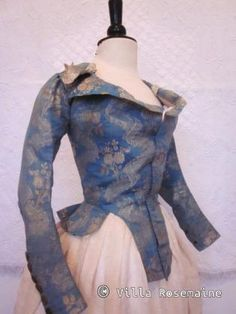 """Pierrot à la hussarde"" jacket, France, 1780-1790. Nattier blue silk taffeta with a woven pattern of bouquets, trimmed with ivory silk ribbon on the pass, steel buttons on each wrist, linen lining."
