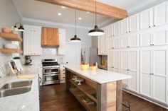 Fixer Upper - Country kitchen with black barn pendants illuminating salvaged wood island with shelves topped with white and gray countertops situated across from wall of floor to ceiling pantry cabinets with oil-rubbed bronze hardware. White shaker cabinets paired with subway tiled backsplash flank reclaimed wood hood over stainless steel stove with double ovens.