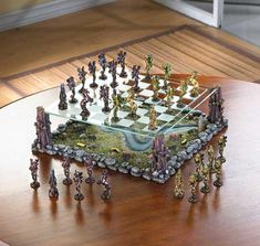"""In this legendary world of the """"Faerie Chess"""", the armies of two ancient kings gather for a mythical battle. Across the fields and woods they march, matching wits and force as players in the age-old classic strategy game of chess. This stunning set is sure to be the envy of all, with a clear etched-glass board suspended above a lifelike sculpted landscape. Each playing piece is a miniature masterpiece, suitable for displaying with pride! 16"""" x 16"""" x 5"""" high."""