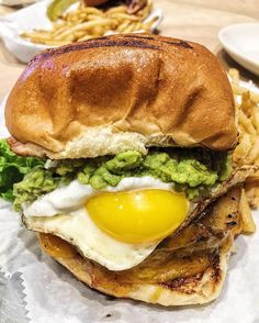 Hotel California Cheeseburger topped with a fried egg, guacamole, grilled onions, cheddar cheese, jalapeño relish, and cilantro sour cream on a brioche bun!