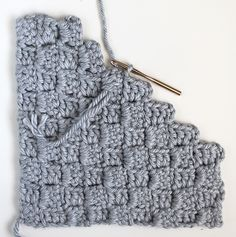 A free crochet pattern for a textured, modern, trendy crochet throw pillow with a stairstep stitch pattern. Use extra bulky yarn and a size N crochet hook and this crochet project will be done quickly!