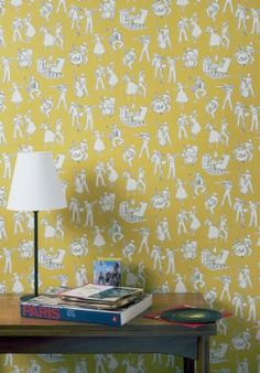 Lewis and Wood -  Lewis And Wood Fabric Collection - Mustard yellow, white and grey patterned wallpaper behind a simple wooden table with a white table lamp, books and records