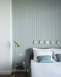 Pale blue is a wonderfully calm colour in a master bedroom. To add interest, use a narrow wooden panelling to create a feature wall behind the bed head.