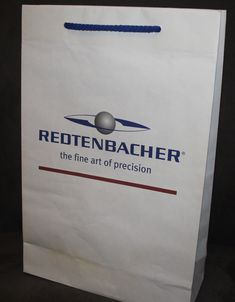 Hier haben wir eine Papiertüte aus Naturpapier bedruckt mit einem 2-farbigen Druck sowie einer handlangen passenden blauen Baumwollkordel Bottle Opener, Cardboard Packaging, Company Logo, Present Wrapping, Tote Bag, Packaging, Gifts