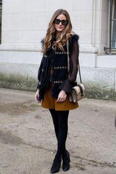 Olivia Palermo con shorts en color mostaza, camisa negra de mangas transparentes y chaleco de pelo.