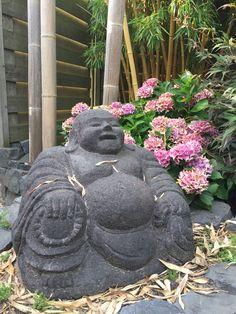 Boeddha onder de bladeren van de bamboe uitlopers