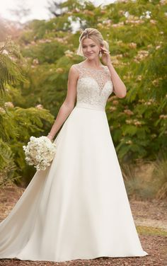 Traditional and glamorous, this Twilight Mikado ball gown with embellished boat neck from Essense of Australia is a stand out! A plunging sweetheart neckline is covered by a Diamante-beaded, high illusion neckline, giving a look that is elegant with a hint of sexy. A coordinating belt highlights the waist before the full, A-line skirt - with pockets - flows out into a simple train. The back of the gown features illusion-lace detailing and zips up beneath fabric and Diamante buttons…