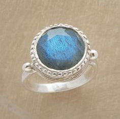EYE OF PARADISE RING -- Iridescent blue labradorite, faceted with a flat table, glimmers in a high stacked bezel with fine rope edge. Oxidized sterling silver. Handmade. Exclusive. Whole sizes 5 to 9.