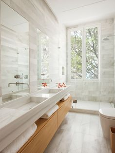 In this modern bathroom there's a wooden bathroom vanity with open shelving, that has double sinks with tall rectangular mirrors above each one. A glass shower surround allows the light from the vertical windows to pass through and fill the room, while st Wooden Bathroom Vanity, Small Bathroom, Bathroom Ideas, Master Bathroom, Bathroom Modern, Mirror Bathroom, Bathroom Lighting, Bathroom Remodeling, Wood Vanity
