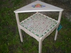 Small side table painted a pale pink.  Bottom shelf tiled with broken china and coated for durability.