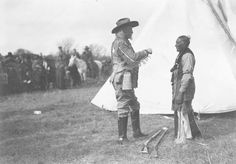 William F. Cody speaking to a Native American during the filming of a movie about the Indian Wars.