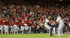 Cardinals closer Jason Motte (right) embraces catcher Tony Cruz as their teammates rush the field after Game 5 of the National League Division Series between the St. Louis Cardinals and the Washington Nationals on Friday, Oct. 12, 2012, at Nationals Park in Washington, D.C.